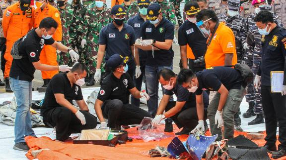 Rescue workers inspect recovered items and debris at a port in Jakarta.