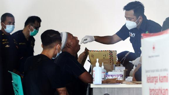 A man is swabbed for his DNA sample at Supadio International Airport. It is to help with the identification of victims.