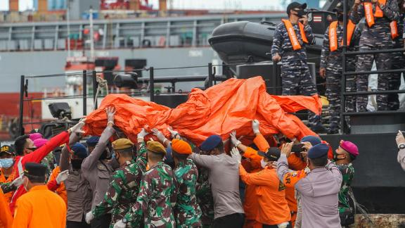 TOPSHOT - Rescue workers carry recovered debris at the port in Jakarta on January 10, 2021, during the search operation for Sriwijaya Air flight SJY182 which crashed after takeoff from Jakarta on January 9. (Photo by Dany Krisnadhi / AFP) (Photo by DANY KRISNADHI/AFP via Getty Images)