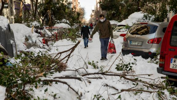 People walk along a road with fallen branches a day after the heaviest snowfall in decades on January 10 in Madrid, Spain.