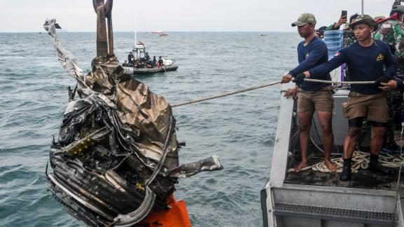 Members of the Indonesian Navy retrieve a piece of debris while searching for the remains of the plane on Monday, January 11.