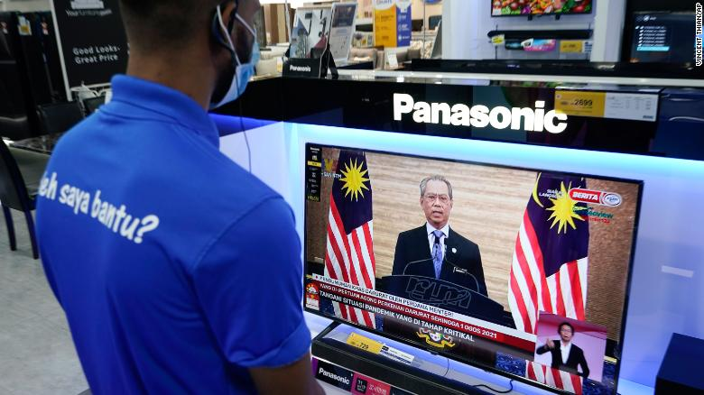 An electronic shop worker watches a live broadcast of Malaysian Prime Minister Muhyiddin Yassin in Kuala Lumpur, Malaysia on January 12.