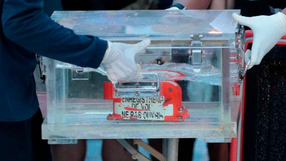 Members of Indonesia's National Transportation Safety Committee carry a box containing the flight data recorder from Sriwijaya Air Flight 182 after the recorder was retrieved from the Java Sea on Tuesday, January 12.