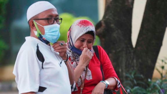 Relatives of Panca Widia Nursanti, one of the crash victims, react at a hospital in Jakarta on January 12.