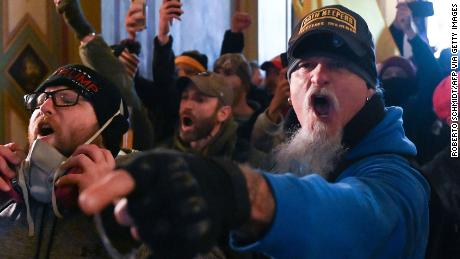 A man wearing an Oath Keepers hat is among the mob inside the US Capitol on January 6 in Washington, DC. The Oath Keepers is a pro-Trump, far-right, anti-government group that tries to recruit members from active or retired military.