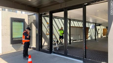 Crews at New Zealand's Parliament inspect the smashed front doors on January 13 in Wellington.