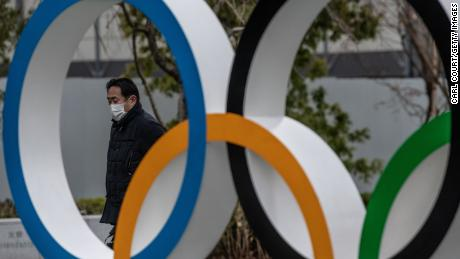 TOKYO, JAPAN - JANUARY 12: A man wearing a face mask walks past the Olympic Rings on January 12, 2021 in Tokyo, Japan. Recent surveys by Kyodo News and Tokyo Broadcasting System found that over 80 percent of people in Japan who were questioned believe the Tokyo Olympics should be cancelled or postponed or that the Olympics will not take place. Tokyo remains in a second state of emergency amid a third wave of Covid-19 coronavirus that has seen infection rates climb to unprecedented levels. (Photo by Carl Court/Getty Images)
