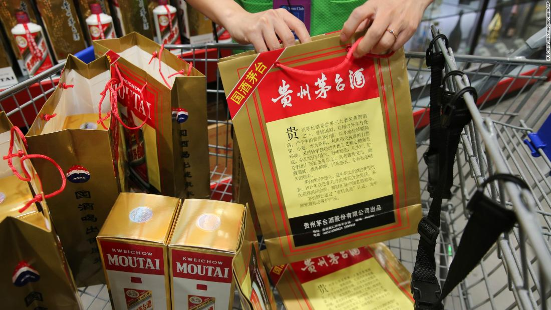 An employee displays China's leading liquor maker Kweichow Moutai at a supermarket in Nantong city, in China's Jiangsu province in 2018.