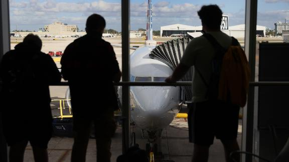 Passengers look out at American Airlines flight 718, a Boeing 737 Max, parked at its gate at Miami International Airport as people load for the flight to New York on December 29, 2020 in Miami, Florida. The Boeing 737 Max flew its first commercial flight since the aircraft was allowed to return to service nearly two years after being grounded worldwide following a pair of separate crashes. (Photo by Joe Raedle/Getty Images)