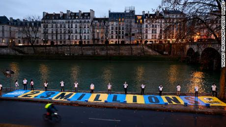 Activists unfurled a banner outside a Paris courthouse Thursday.