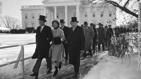 John F. Kennedy and Jacqueline Kennedy, along with others, walk to JFK's Inauguration Day ceremony in Washington, DC on January 20, 1961.