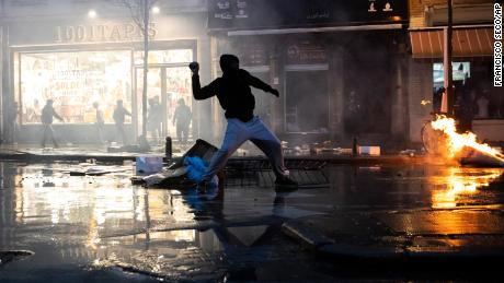 Rioters throw stones toward a police office in the Belgium capital, Brussels, Wednesday, Jan. 13, 2021, at the end of a protest asking for authorities to shed light on the circumstances surrounding the death of a 23-year-old Black man who was detained by police last week in Brussels. Police in Brussels made more than 100 arrests after a demonstration in Brussels over the death of a young Black man while in police custody turned violent Wednesday. (AP Photo/Francisco Seco)