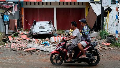 Pengendara melewati reruntuhan mobil yang rusak akibat gempa di Mamuju, Sulawesi Barat, Indonesia.
