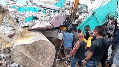 Tim penyelamat mencari korban dari sebuah bangunan runtuh di Mamuju, Indonesia.