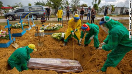 Gravediggers bury a Covid-19 victim while surrounded by relatives at the Nossa Senhora Aparecida cemetery in Manaus on January 13, 2021.