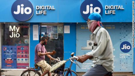 People on bicycle passes by a Jio store in Kolkata, India on July 13, 2020.
