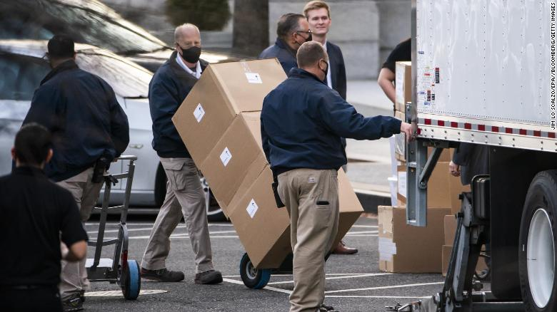 Workers move boxes onto a truck on West Executive Avenue between the White House and the Eisenhower Executive Office Building on Thursday, Jan. 14, 2021.