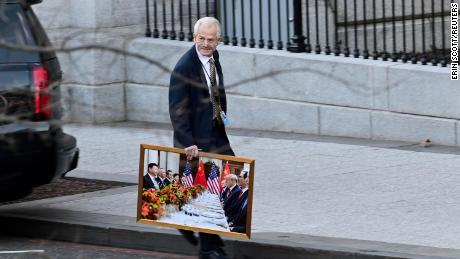 White House Adviser Peter Navarro leaves the West Wing of the White House with a photo of US President Donald Trump and Chinese President Xi Jinping in Washington, DC, USA, January 13, 2021.