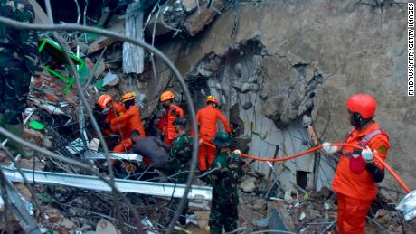 Rescuers search for survivors at a collapsed building in Mamuju on January 15, 2021, after a 6.2-magnitude earthquake rocked Indonesia's Sulawesi Island.
