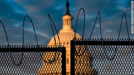 The US Capitol is seen behind a fence topped with razor wire on Saturday in Washington.