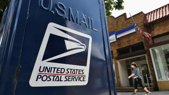 A woman walks past mailboxes  seen outside of a US Post Office in Washington, DC on August 17, 2020. - The United States Postal Service is popularly known for delivering mail despite snow, rain or heat, but it faces a new foe in President Donald Trump. Ahead of the November 3 elections in which millions of voters are expected to cast ballots by mail due to the coronavirus, Trump has leveled an unprecedented attack at the USPS, opposing efforts to give the cash-strapped agency more money as part of a big new virus-related stimulus package, even as changes there have caused delays in mail delivery. (Photo by MANDEL NGAN / AFP) (Photo by MANDEL NGAN/AFP via Getty Images)