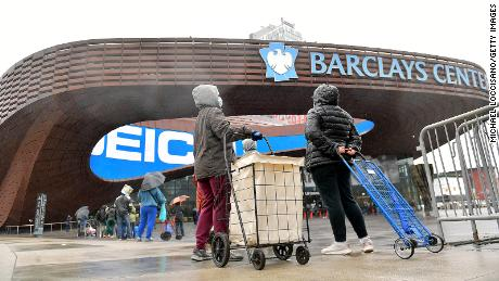 People await access to a mobile food pantry at Barclays Center in Brooklyn, New York, on April 24.