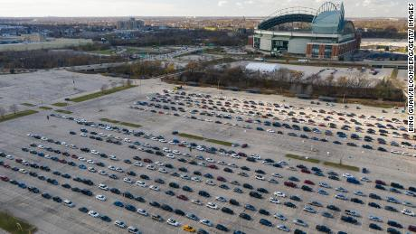 People in vehicles wait to enter a drive-thru Covid-19 testing site at Miller Park in Milwaukee, Wisconsin.