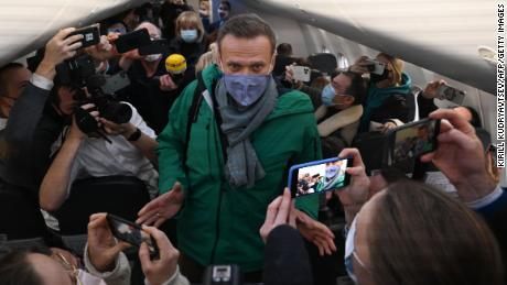 Passengers and journalists take photos of Alexey Navalny as he takes his seat on the flight Sunday.
