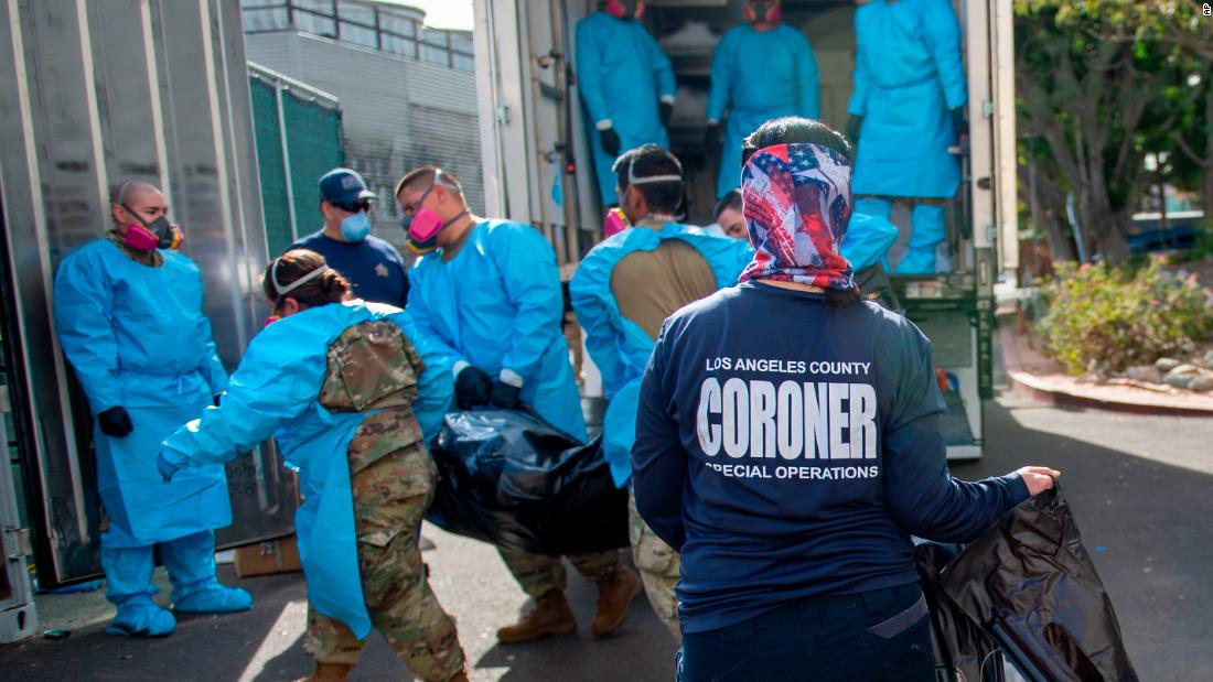 Elizabeth Napoles, right, works with National Guardsmen who are helping to process Covid-19 deaths to be placed into temporary storage in Los Angeles on Tuesday, January 12.