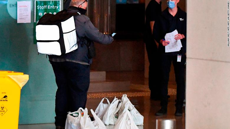 Seorang pekerja pengiriman makanan mengantarkan makanan ke sebuah hotel di Melbourne pada 17 Januari 2021, di mana para pemain dikarantina selama dua minggu menjelang turnamen tenis Australia Terbuka.