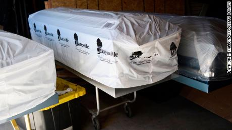 "Covered empty caskets stand in a garage at the Boyd Funeral Home during a surge of Covid-19 deaths on January 14, 2021 in Los Angeles, California. - A corpse in the break room. Embalmed bodies in the garage.  Boyd Funeral Home, a small family business in Los Angeles, is so overflowing with Covid-19 victims it has begun turning away customers for the first time in its history. ""The weekend before I turned down 16 families that I couldn't do services for,"" said owner Candy Boyd.  ""It's sad. But that's pretty much how it is now."" (Photo by Patrick T. FALLON / AFP) (Photo by PATRICK T. FALLON/AFP via Getty Images)"