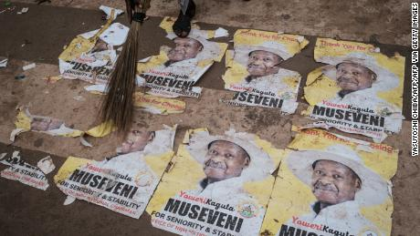 A worker sweeps the ground covered with campaign posters of President Yoweri Museveni on January 17, 2021 on a street in Kampala, Uganda.