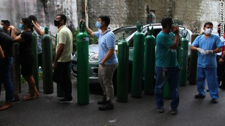 Family members of patients hospitalized with Covid-19 line up with empty oxygen tanks in an attempt to refill them in Manaus, Amazonas state, Brazil on January 15