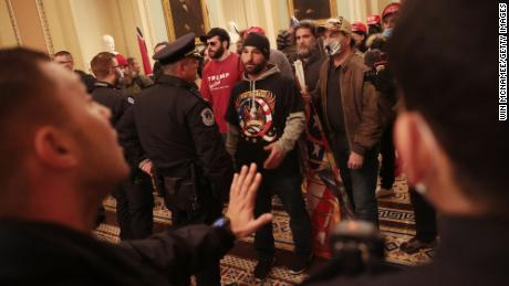 Protesters interact with Capitol Police inside the US Capitol Building.