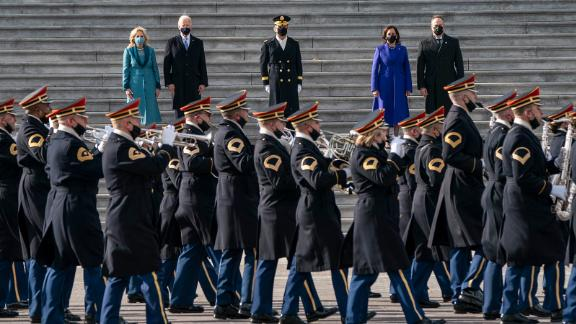 A band parades past the new president and vice president.