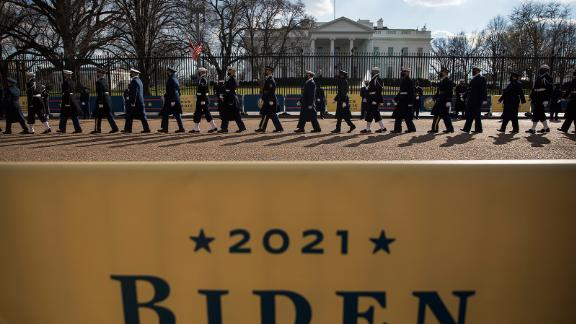 Members of the military walk past the White House during Biden's abbreviated parade on Wednesday.