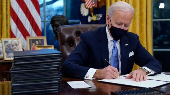 President Joe Biden signs his first executive order in the Oval Office of the White House on Wednesday, Jan. 20, 2021, in Washington. (AP Photo/Evan Vucci)