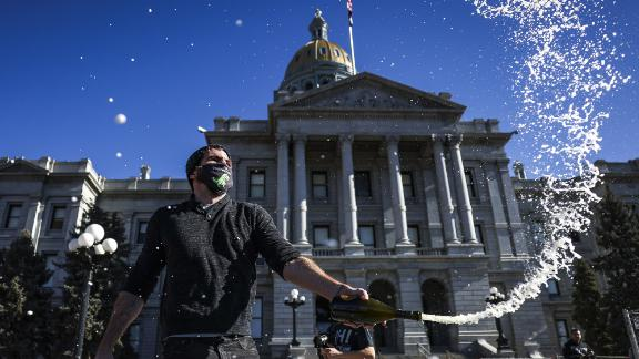 Keith Hodson pops a bottle of champagne on the steps of the Colorado State Capitol in Denver on Wednesday.
