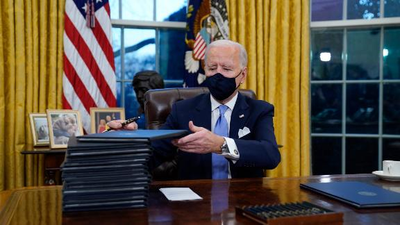 """Biden signs executive orders in the Oval Office after his inauguration. """"There's no time to start like today,"""" Biden told reporters as he began signing a stack of orders and memoranda. """"I'm going to start by keeping the promises I made to the American people."""""""