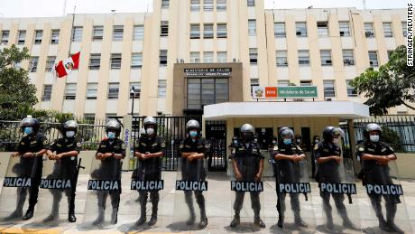 Police stand guard outside the Ministry of Health as health workers protest in Peru on January 13.