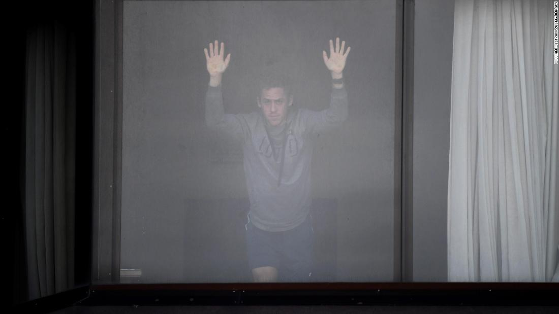 A tennis player waits for a training session from his hotel in Melbourne on January 19. Dozens of players had to quarantine in hotels ahead of the Australian Open.