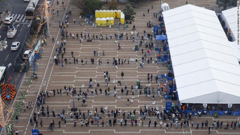 People queue outside a Covid-19 mass vaccination center at Rabin Square in this aerial photograph taken in Tel Aviv on January 4, 2020.