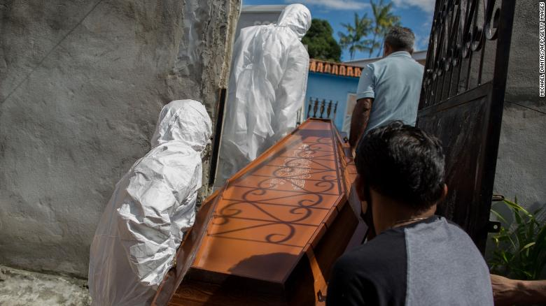 Municipal workers remove the body of 75-year-old Adamor Mendonca Maciel from his home in Manaus, Brazil, on January 16, 2021 after he died of Covid-19.