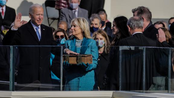 Biden raises his right hand as he takes the oath of office.