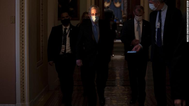 Senate Minority Leader Mitch McConnell, center, wears a protective mask while walking to his office from the Senate Chamber at the U.S. Capitol in Washington, D.C., U.S., on Thursday, Jan. 21, 2021.