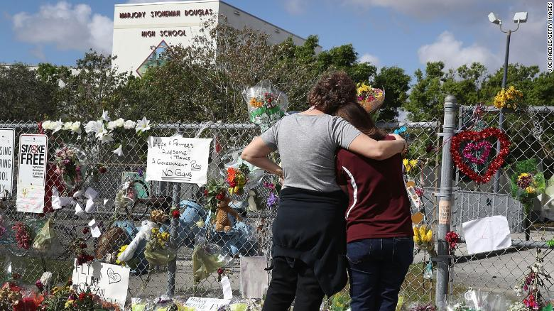 Margarita Lasalle, right, the budget keeper, and Joellen Berman, the guidance data specialist, look on at the memorial in front of Marjory Stoneman Douglas High School as teachers and staff are allowed to return to the school for the first time since the mass shooting on campus on February 23, 2018 in Parkland, Florida.