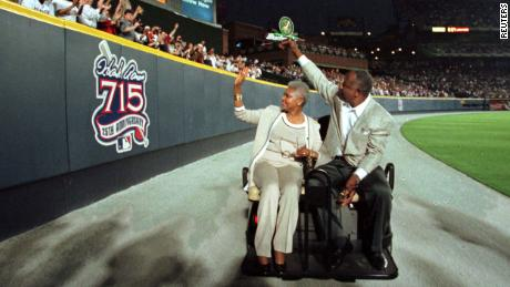 Aaron and his wife, Billye, wave to fans as they pass a sign honoring Aaron on the outfield wall at Turner Field after a ceremony honoring the 25th anniversary of Aaron's record-breaking home run.