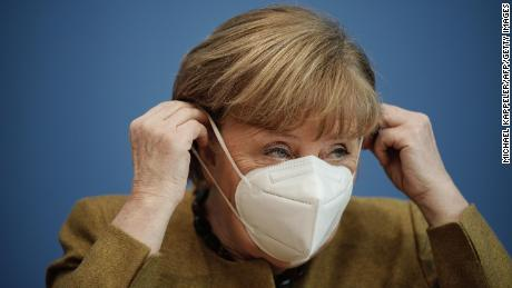 German Chancellor Angela Merkel puts on her face mask after giving a press briefing on the Covid-19 situation on Thursday.