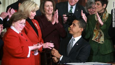 President Barack Obama hands Lilly Ledbetter a pen after signing the Lilly Ledbetter Fair Pay Act during an event in the East Room of the White House January 29, 2009 in Washington, DC.