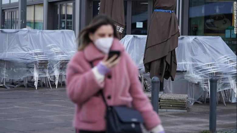A woman wearing an FFP2 face mask walks past a shuttered cafe in Berlin, Germany.